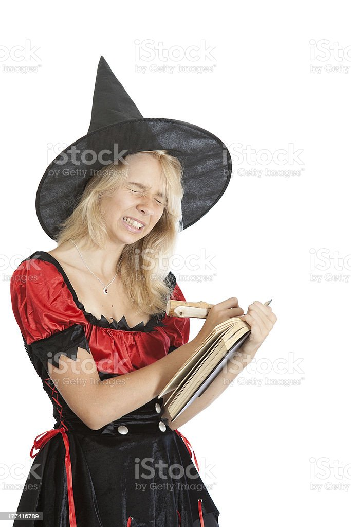 angry teenager girl in Halloween witch reads magic book royalty-free stock photo