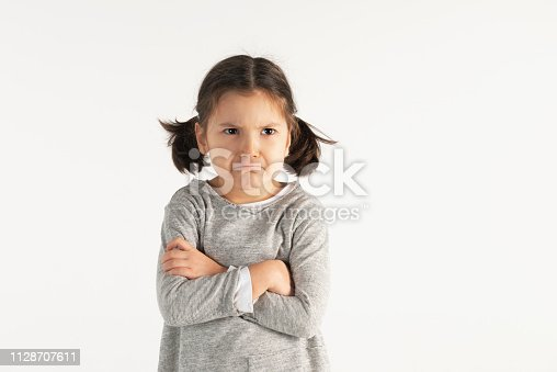 Angry caucasian toddler with crossed arms on white background.