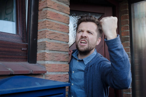 Angry upset young male neighbor with fist in air, open mouth yelling. stock photo
