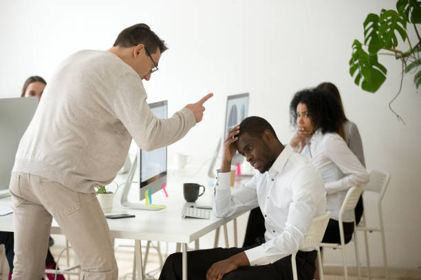 Angry white boss scolding rebuking incompetent black employee in office Angry white boss scolding rebuking incompetent black office employee, dissatisfied ceo shouting at african american worker for bad work or failure, reprimand or racial discrimination at work concept miserly stock pictures, royalty-free photos & images