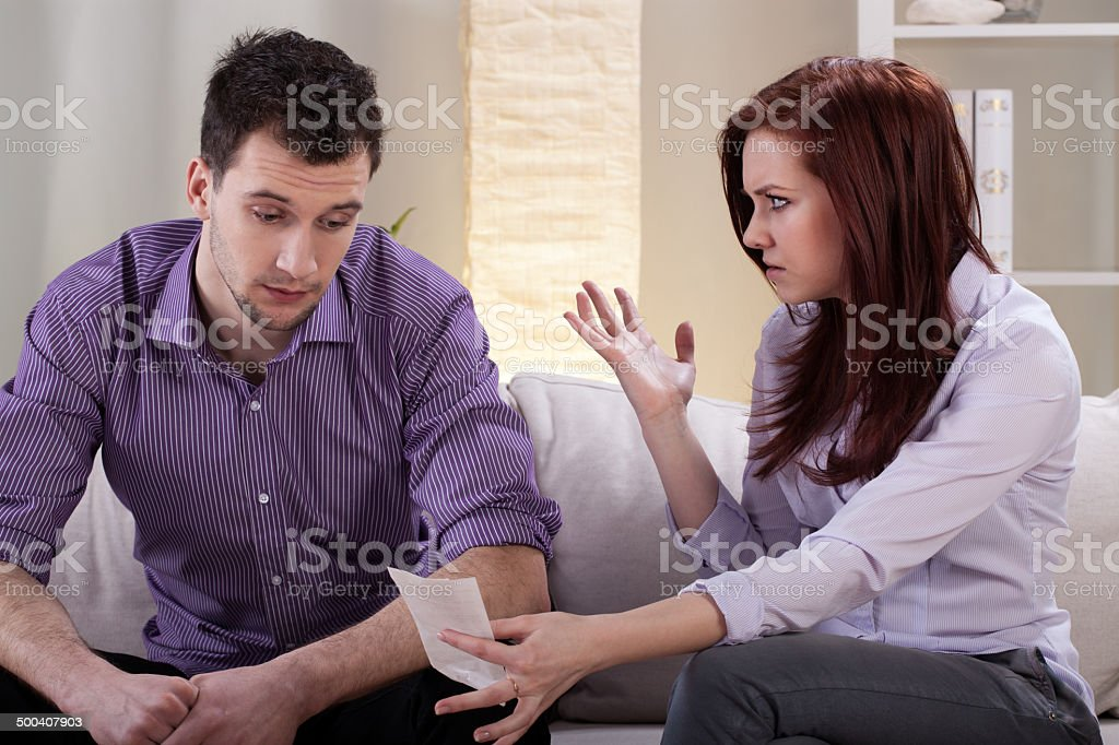 Angry wife showing bills stock photo