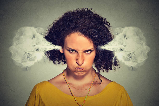 angry woman blowing steam coming out of ears stock photo