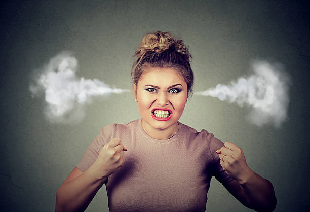 angry woman blowing steam coming out of ears Closeup portrait angry young woman blowing steam coming out of ears, about to have nervous atomic breakdown screaming isolated black background. Negative human emotion face expression feeling attitude anger stock pictures, royalty-free photos & images