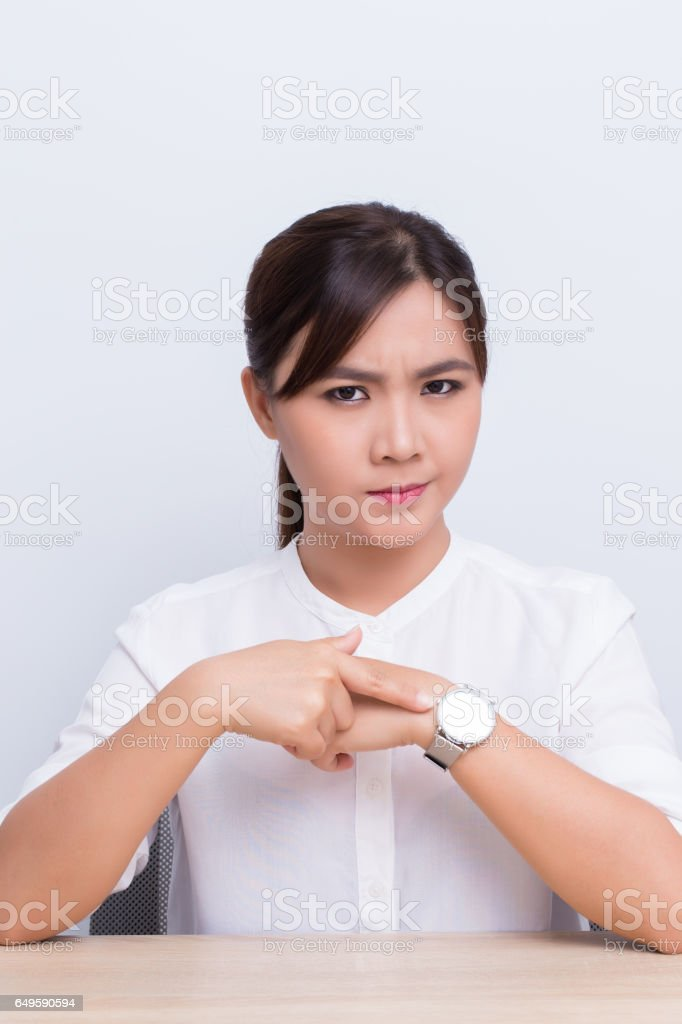Angry woman checking time at office stock photo
