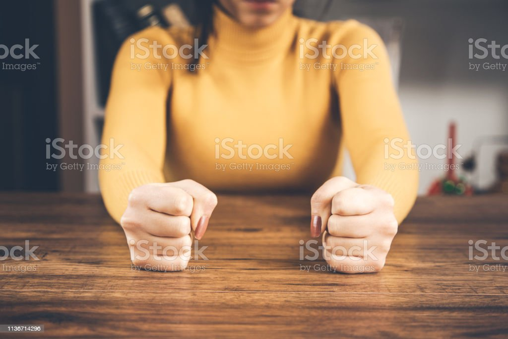 angry woman fists on table
