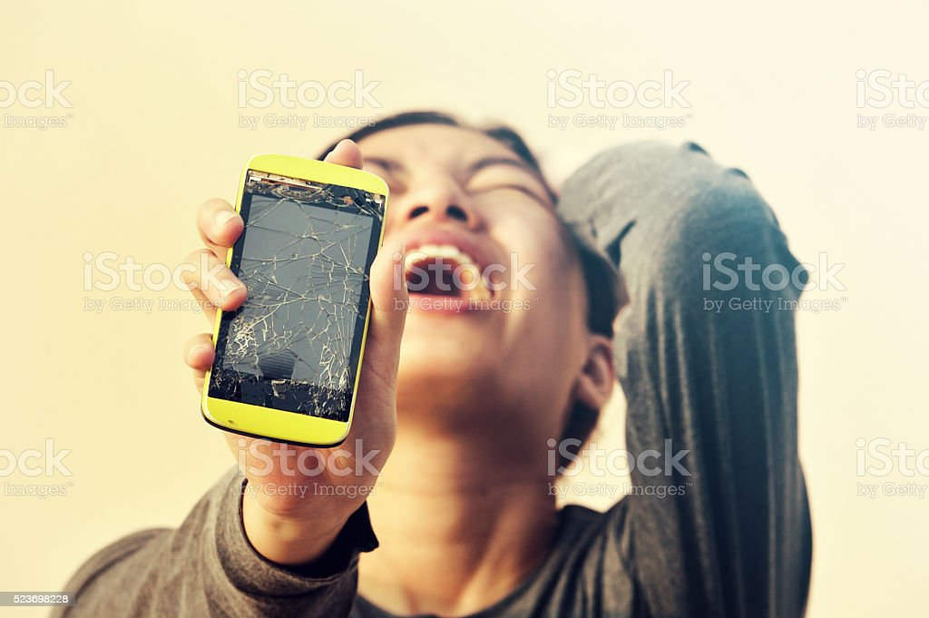 Angry woman holding broken smartphone stock photo