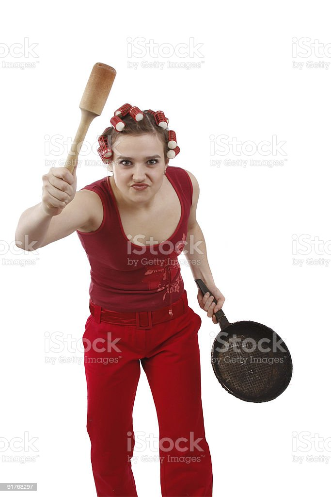 Angry woman in hair rollers, holding a frying pan. stock photo