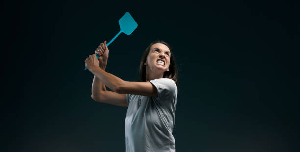 Angry woman killing mosquitoes with a fly swatter stock photo
