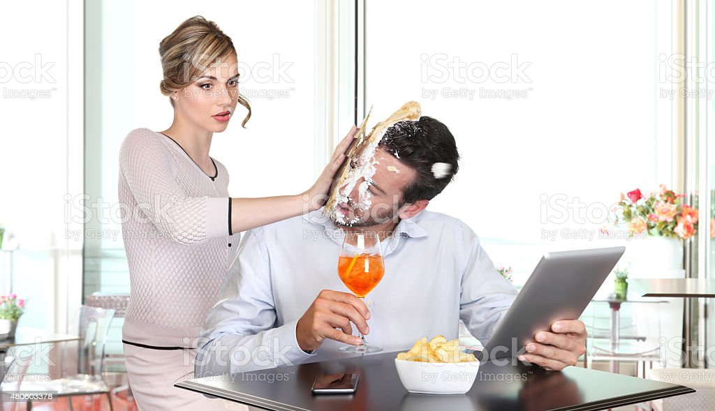 angry woman pulling cake in face to boyfriend cheating stock photo
