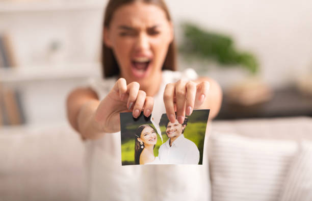 Angry Woman Ripping Photo With Ex-Husband Indoor Divorce. Angry Woman Ripping Wedding Photo With Ex-Husband After Breakup Indoor. Selective Focus former stock pictures, royalty-free photos & images
