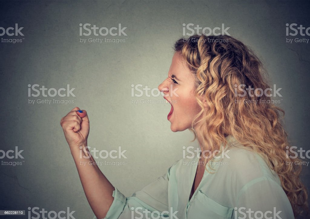 Angry woman screaming with fist up in air royalty-free stock photo
