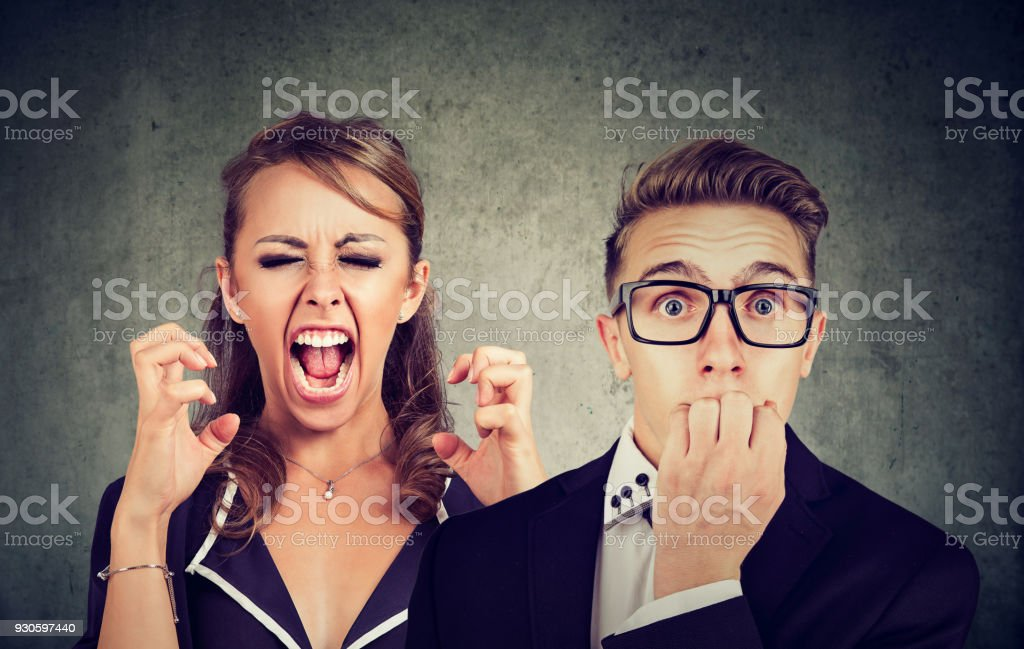 Angry woman shouting and fearful man stock photo