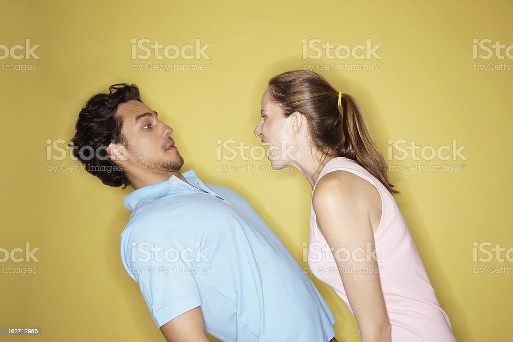 Angry woman shouting at a man against yellow background stock photo