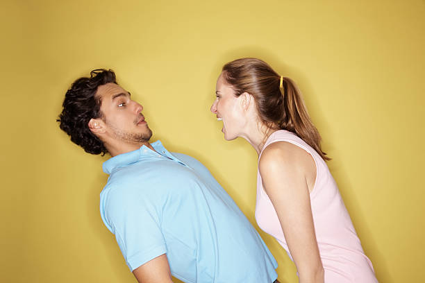 叫ぶに怒っている女性、男性と黄色背景 - ガールフレンド ストックフォトと画像