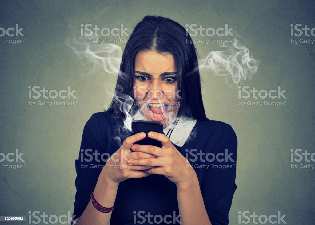 angry woman shouting at her cell phone, enraged with bad service stock photo