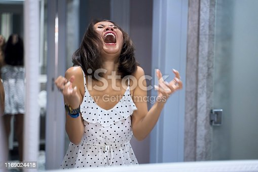 Angry woman shouting at mirror and crying