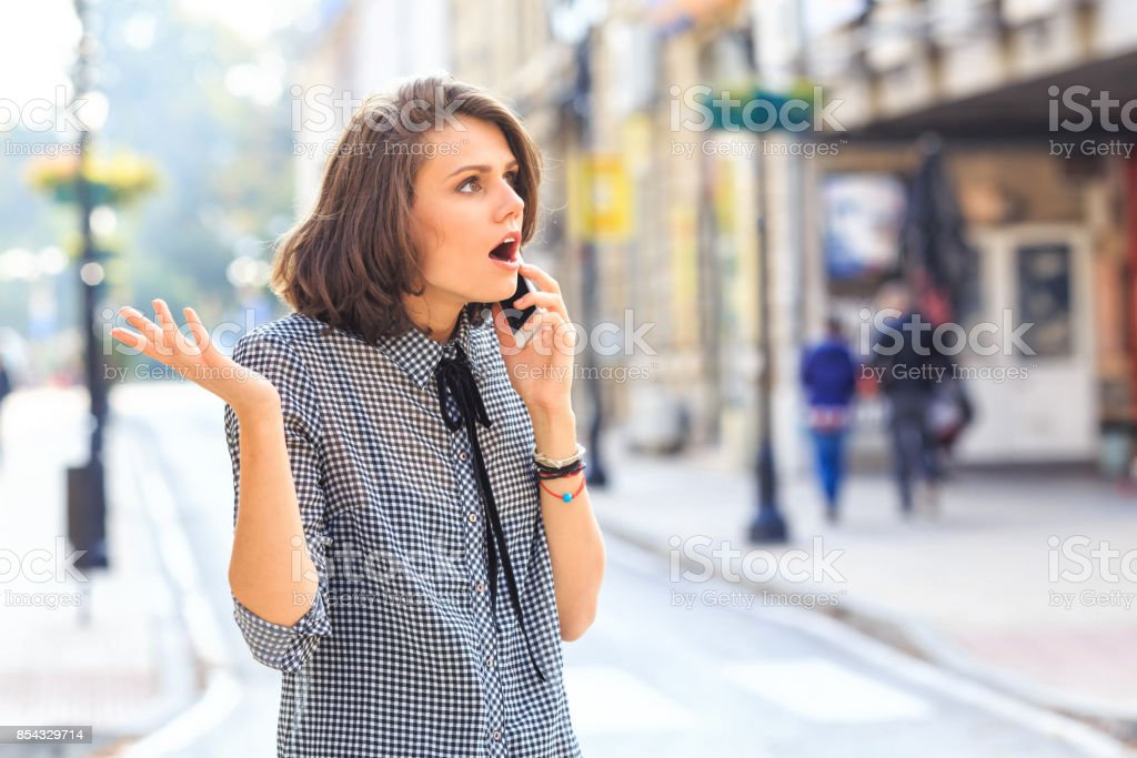 Angry woman talking on smart phone on street stock photo