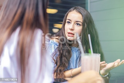 istock angry woman telling her friend what happened 1168279074