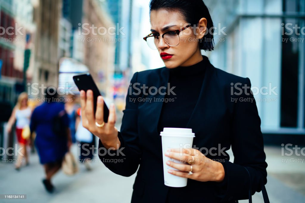 Angry woman trader in optical eyewear reading email with bad news...