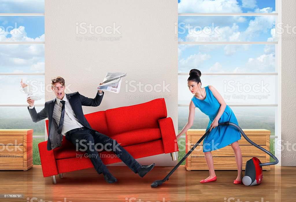 Angry woman vacuuming while man is resting stock photo