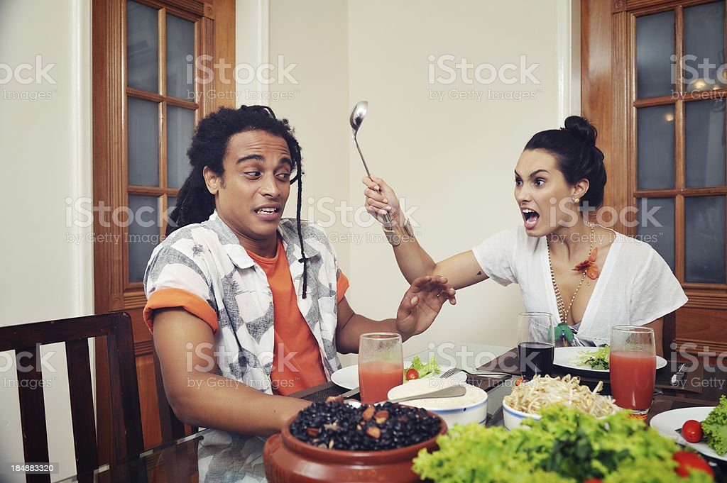Angry Woman wanting to hit her spouse with a spoon royalty-free stock photo