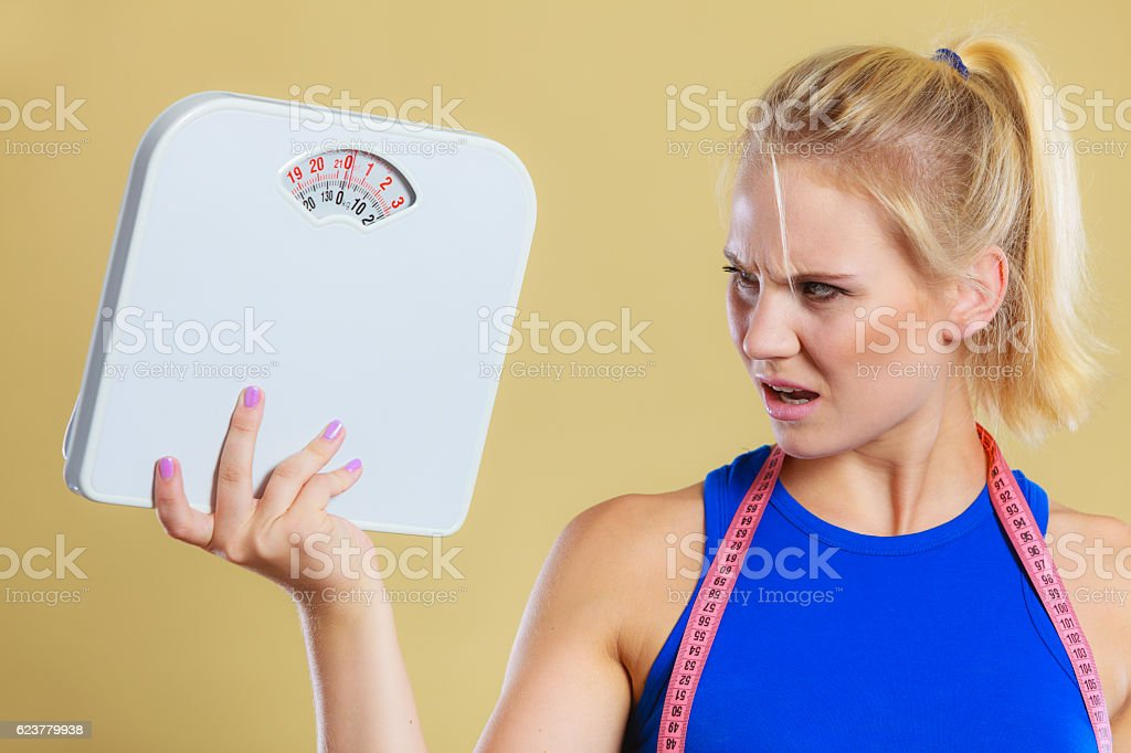 angry woman with scale, weight loss time for slimming stock photo