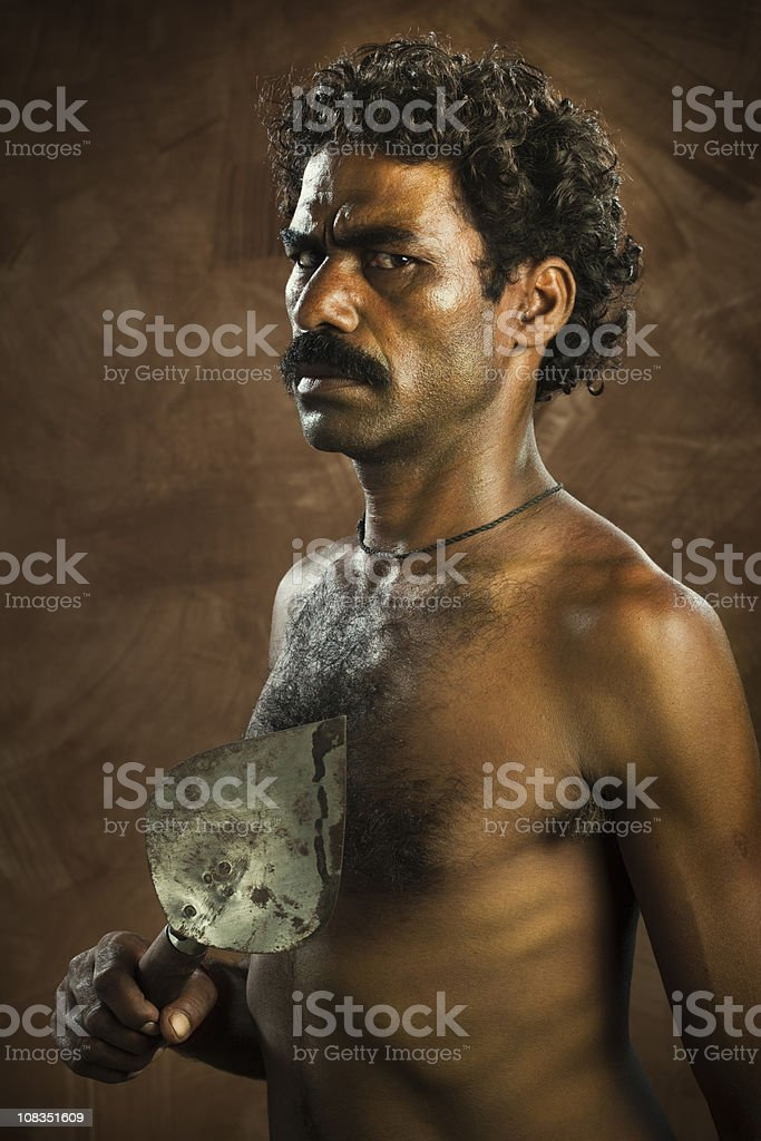 Angry worker holding a work tool stock photo