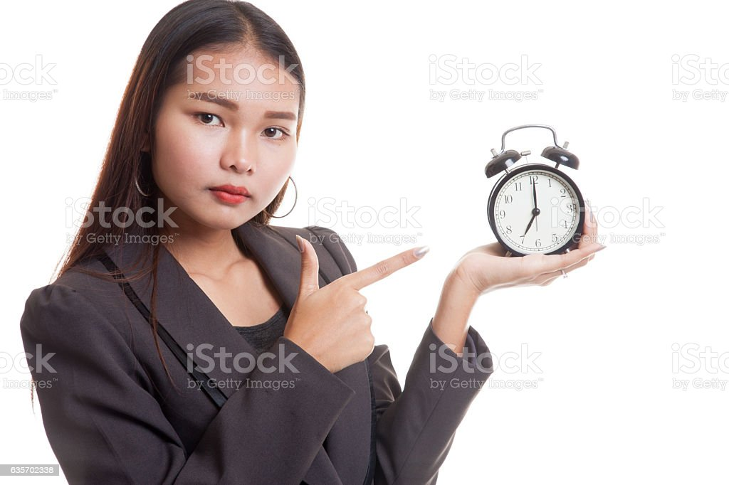 Angry young Asian woman point to a clock. royalty-free stock photo