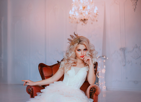 Angry young beautiful girl princess misses sadness loneliness. Queen woman blonde woman long curls hair. Hairstyle with vintage royal crown. Backdrop white room, candelabra romantic lit, bright sparks