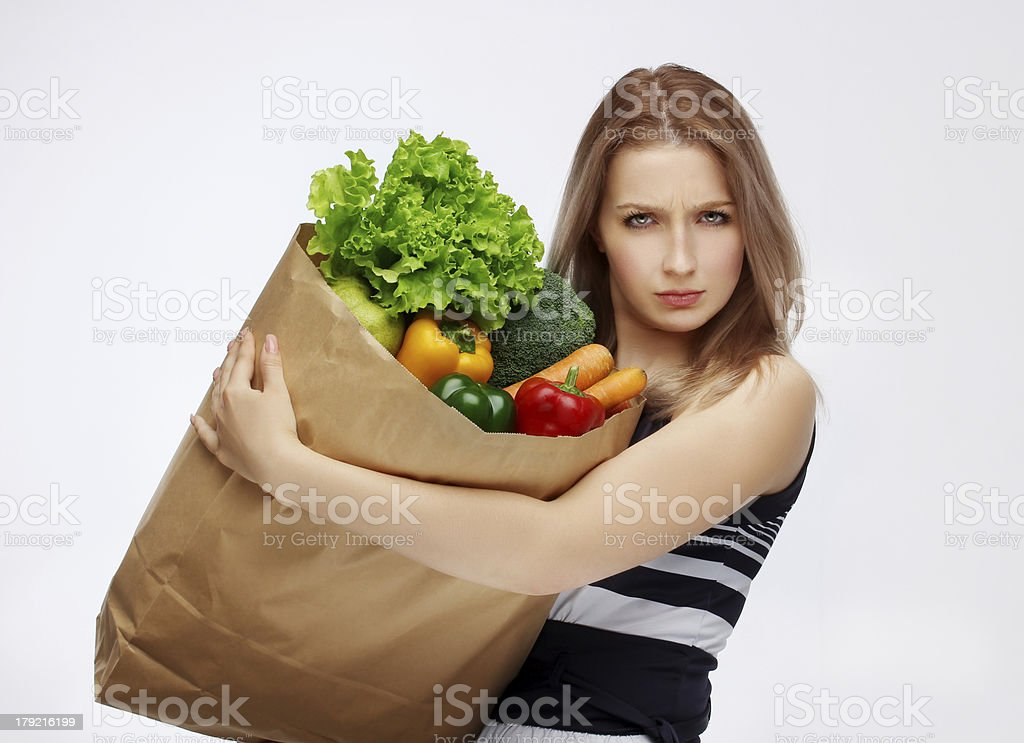 Angry young beautiful woman holding grocery shopping bag royalty-free stock photo