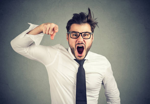 Angry young business man accusing someone screaming stock photo