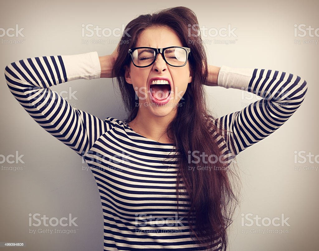 Angry young business woman in glasses strong screaming stock photo
