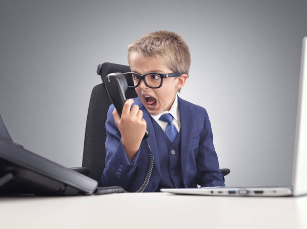 Angry young businessman boy shouting into a phone stock photo