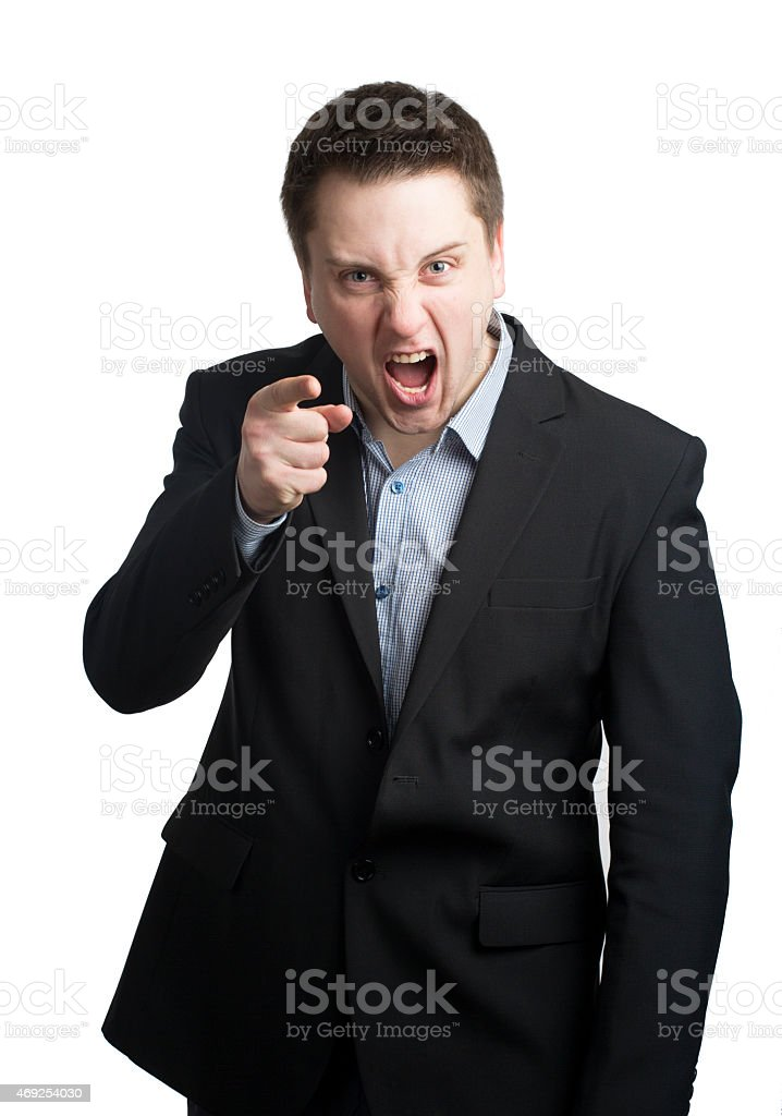 Angry young businessman pointing with his finger and giving out stock photo
