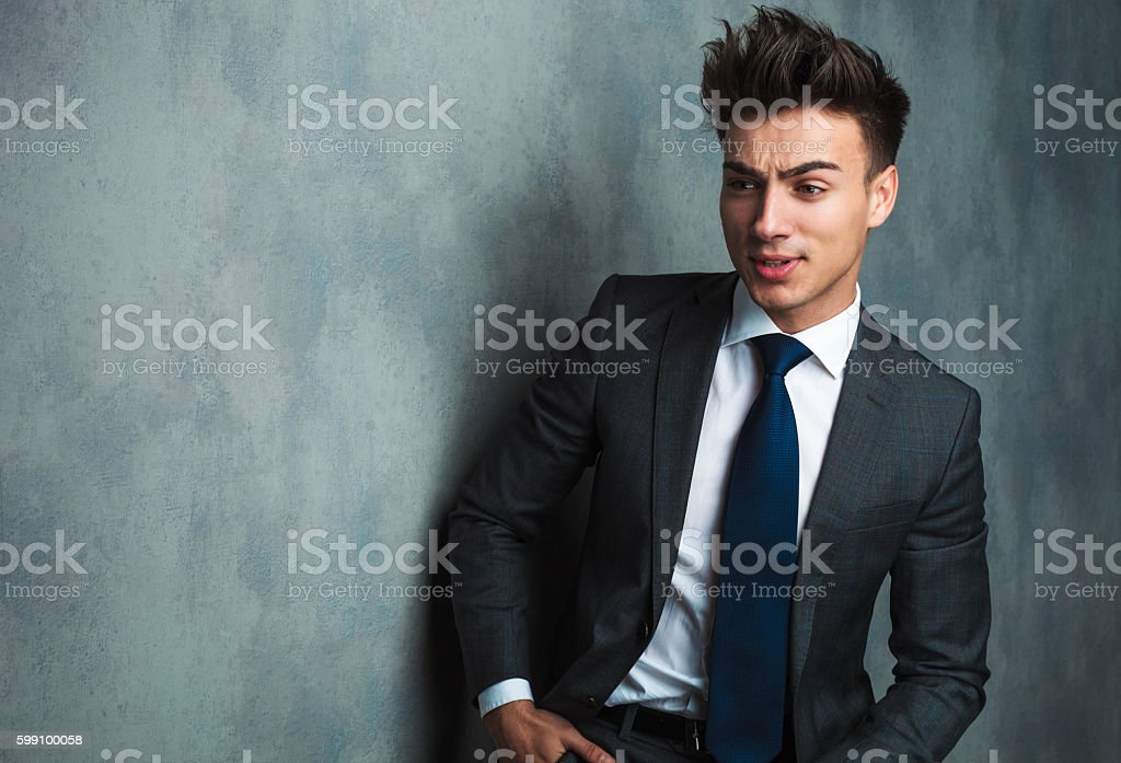 angry young businessman sitting and looking away stock photo