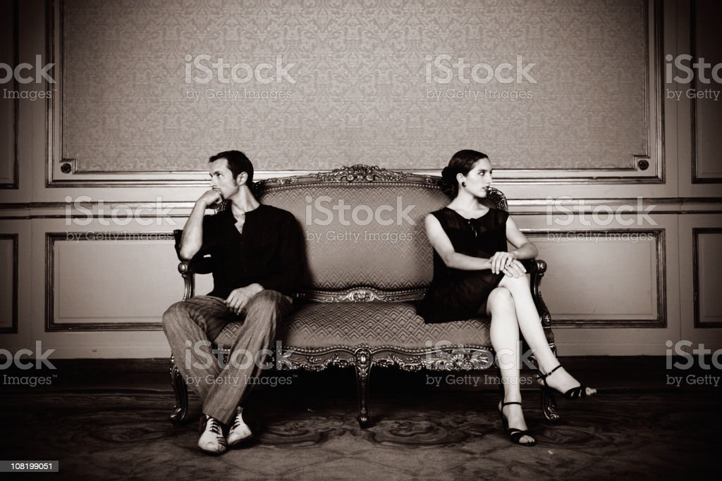 Angry Young Couple Sitting Far on Couch stock photo