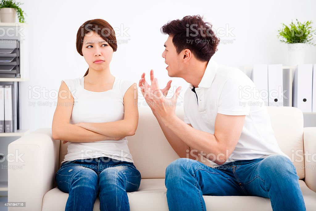Angry young couple sitting on the sofa stock photo