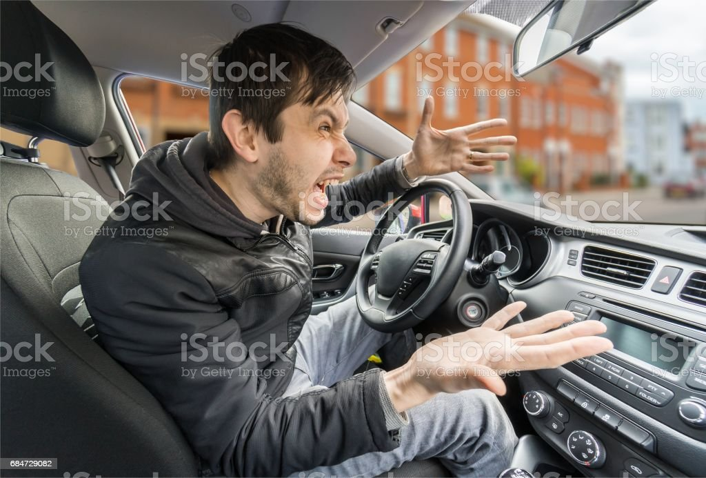 Angry young driver is driving a car and shouting. stock photo