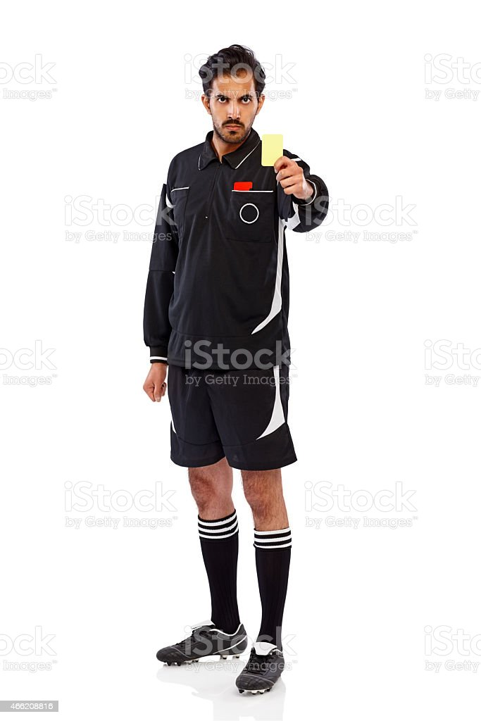 Angry young football referee showing yellow card stock photo