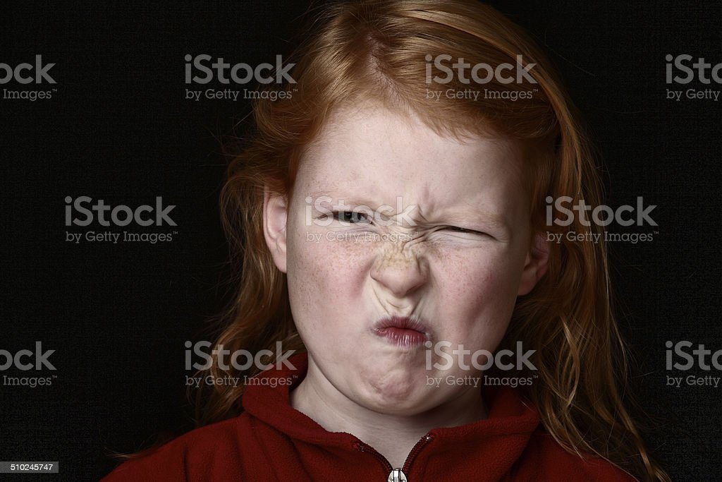 Angry young girl grimacing stock photo