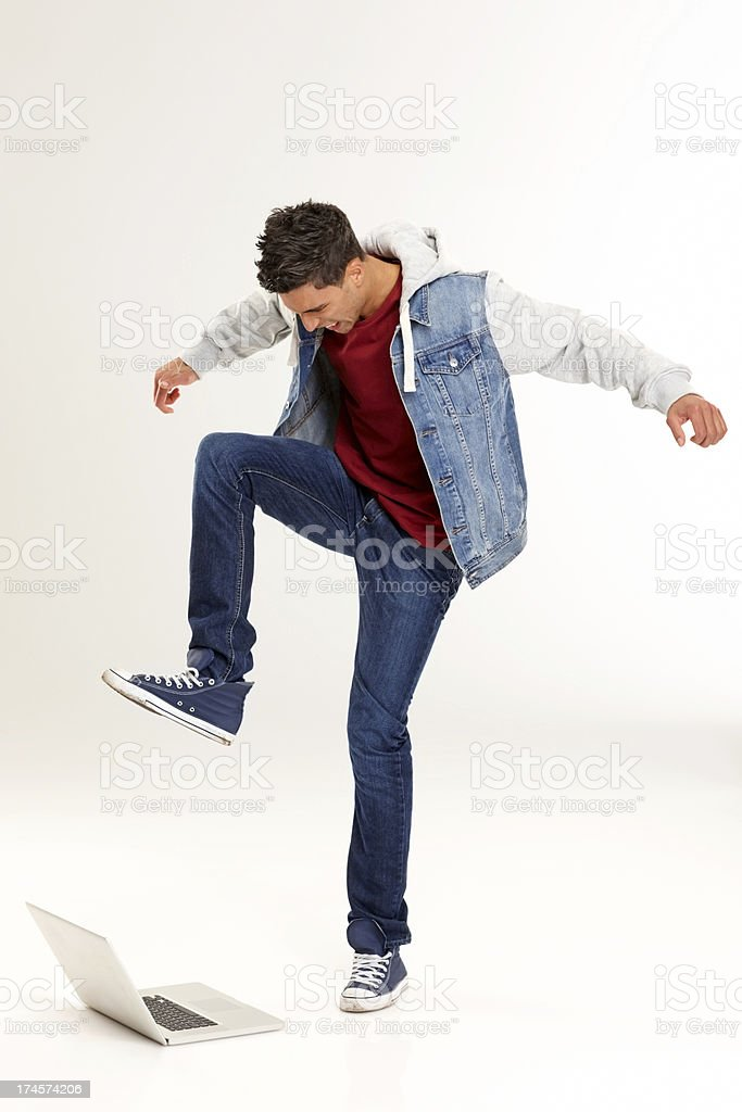 Angry young guy about to crush his laptop royalty-free stock photo