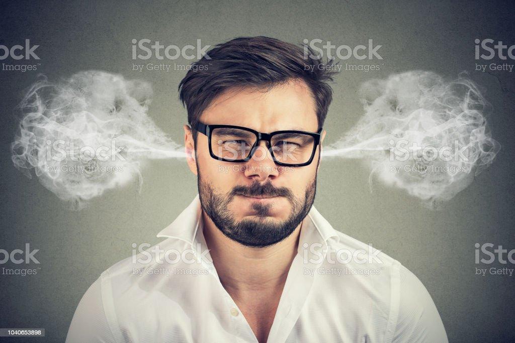 zorniger junger Mann, bläst Dampf aus den Ohren kommt – Foto