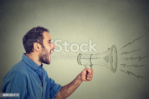 istock angry young man holding screaming in megaphone 668093410