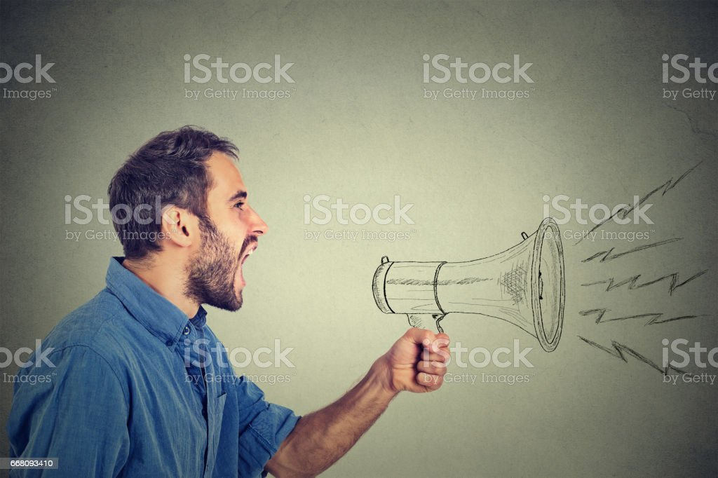 angry young man holding screaming in megaphone stock photo
