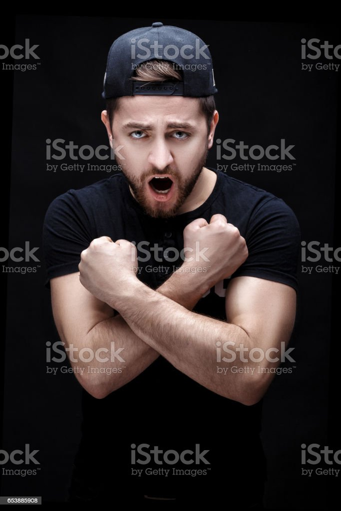 angry young man in the black shirt and cap screaming on black background. stock photo