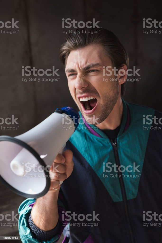 angry young man in vintage windcheater shouting with loudspeaker royalty-free stock photo