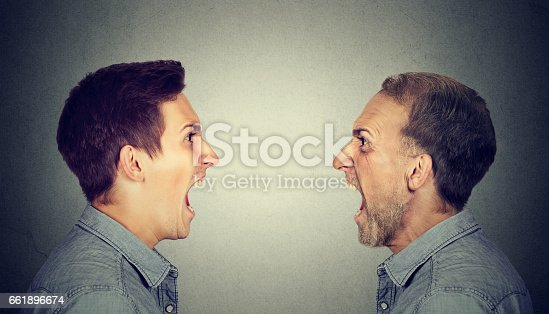 istock Angry young man screaming at old himself 661896674