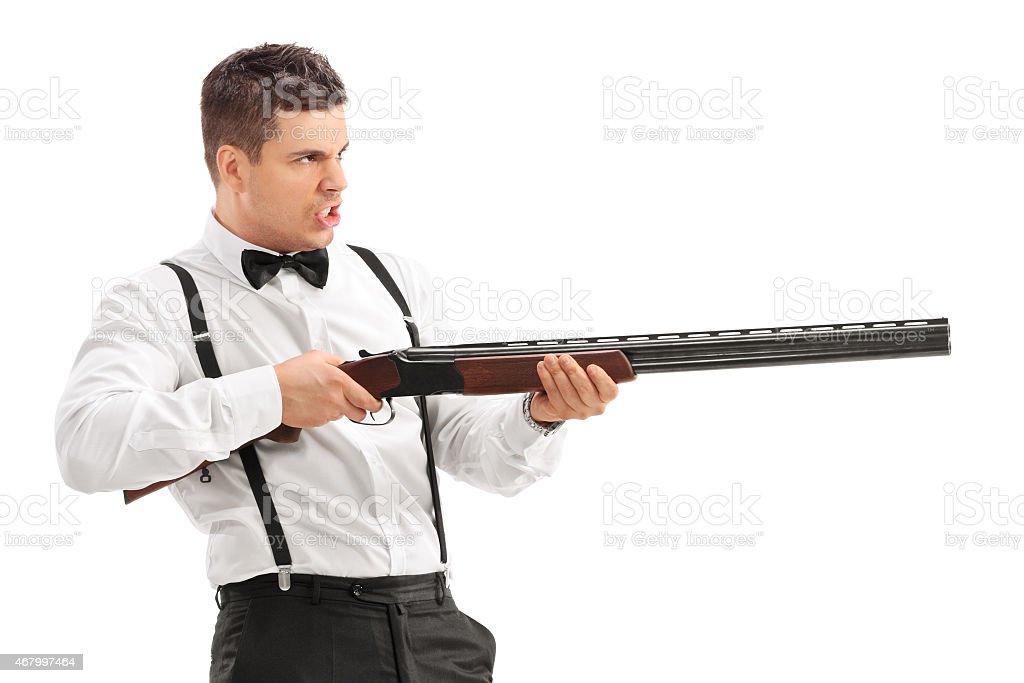 Angry young man shooting with a shotgun stock photo