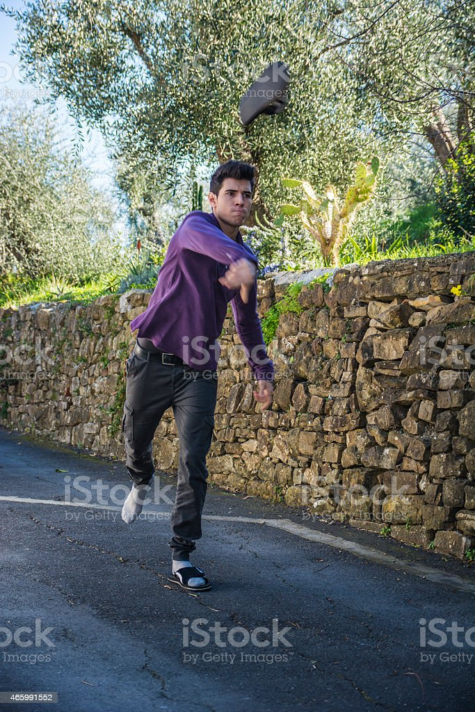 Angry young man tossing his shoe through the air stock photo