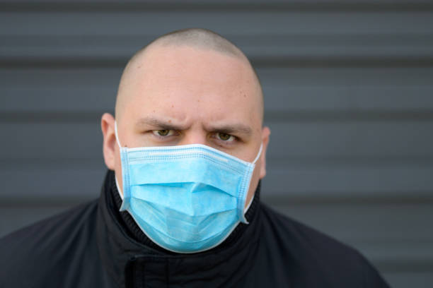 Angry young man wearing a surgical face mask stock photo